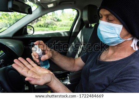 Man using hand sanitizer in the car wearing surgical face mask. Man sitting in the car disinfect his hands to avoid coronavirus infection. #1722484669