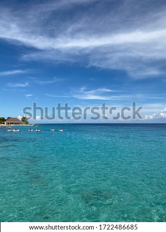 Landscape. View of the blue ocean from the line of the beach. Beautiful natural background. Horizon line of blue sea and sky with clouds. Vertical, cropped image, free space, nobody. Tourism concept.