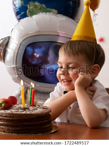 The kid making a wish when blowing out a candle. Image with selective focus and toning