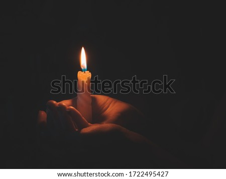 Burning candle in male hand on a black background.  #1722495427