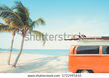 vintage car parked at the tropical beach (seaside) with a surfboard on the roof - Leisure trip in the summer. retro color effect Royalty-Free Stock Photo #1722495610