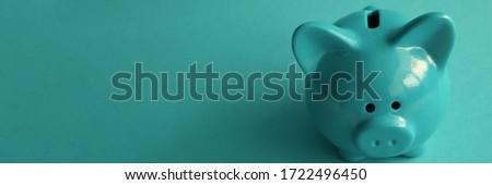 Stylish modern piggy bank on a turquoise background closeup #1722496450