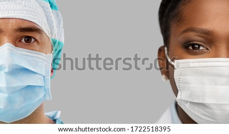 medicine, profession and healthcare concept - close up of african female and hispanic male doctors wearing face medical masks for protection from virus disease over grey background #1722518395