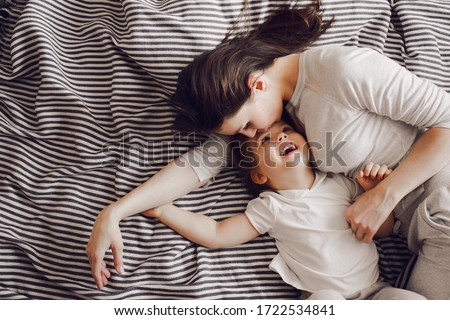beautiful mother with 3 year old daughter hug and laugh while lying on the striped bed #1722534841