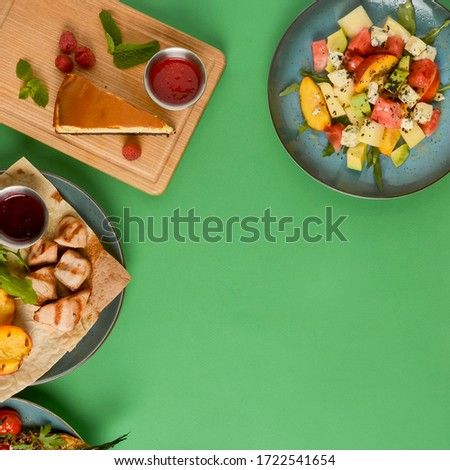 Holiday celebration table setting with food. Flat-lay of sweet cheesecake, fruit salad, meat dishes. Top view of different meals over bright green background. Copy space banner. Frame picture.