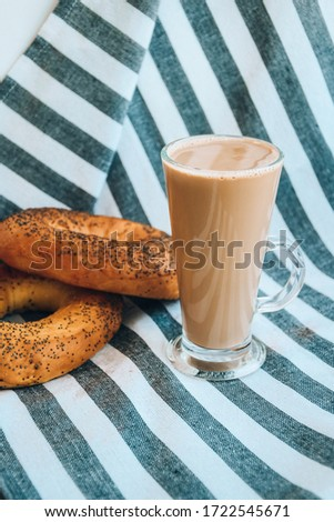 Fresh homemade Poppy bagels bread with cup of coffee, latte machiato or cocoa, cappuccino, breakfast time, Crispy crunchy bagel simits, hot brewed cup of coffee, Traditional Turkish cuisine culture #1722545671