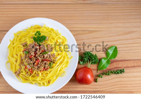 Stir fried pork stir-fried spaghetti in a white plate and red tomatoes, fresh pepper, kaffir lime leaves, left hand position of the picture On a brown wooden background and copy space