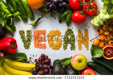 inscription VEGAN from lentils of different types and colors. Fresh vegetables and fruits on a white kitchen table. Background for supermarkets, fresh food stores, delivery. #1722551263