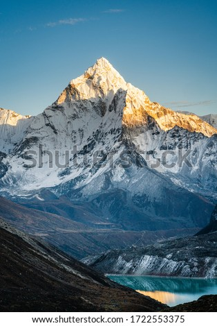 Vertical image of Amadablam mountain peak during sunset and a view of Cholatse glacial lake on the foothills of mountains in Everest region of Nepal. #1722553375