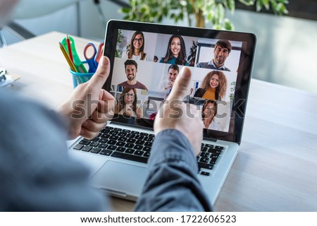 Back view of male employee making a gesturing approval with thumb fingers while speak on video call with diverse colleagues on online briefing with laptop at home. #1722606523