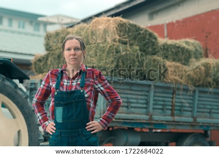 Female farmer posing in front of hay wagon. Portrait of woman farm worker in plaid shirt and bib overalls by the tractor trailer filled with dairy farm livestock feed hay bales. #1722684022