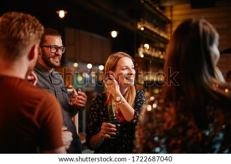 Group of best friends chatting, drinking beer and celebrating at pub. Royalty-Free Stock Photo #1722687040