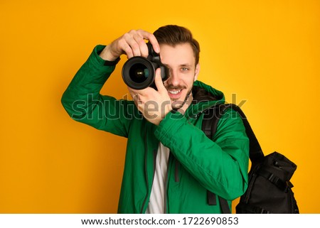 A young photographer in green jacket and white t-shirt with digital camera takes pictures, has a black bag, smiling, is in a good mood, looks through the camera, holding it vertically