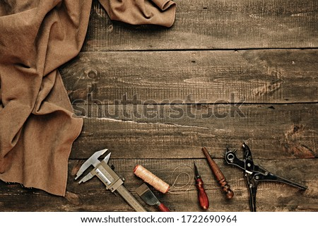 Flat lay composition with leather samples and set crafting DIY tools on wooden table background texture. Leather craftmans work desk. Copy space, maintenance concept. Belt goods production. Top view. Royalty-Free Stock Photo #1722690964