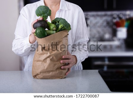Caucasian Woman Holding Brownpaper Bag Full of Green Vegetables Ready for Cooking. #1722700087