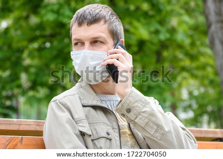 Close-up of masked man with phone on the street #1722704050