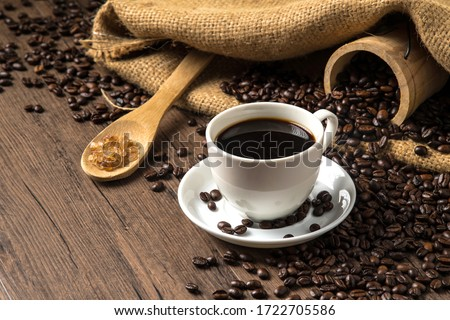 Hot coffee in a white coffee cup and many coffee beans placed around and sugar on a wooden table in a warm, light atmosphere, on dark background, with copy space. #1722705586