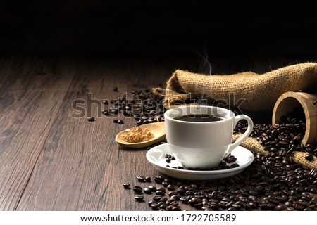 Hot coffee in a white coffee cup and many coffee beans placed around and sugar on a wooden table in a warm, light atmosphere, on dark background, with copy space. #1722705589