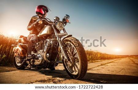 Biker girl on a motorcycle in a leather jacket and a helmet, looks at the way #1722722428
