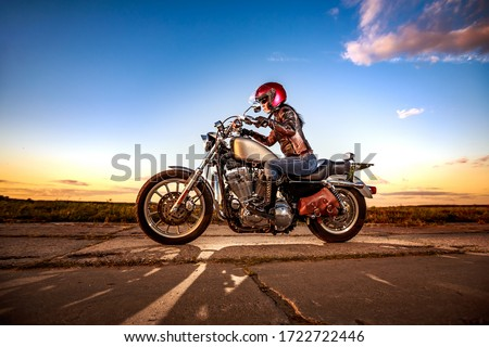 Biker girl in a leather jacket and helmet on a motorcycle #1722722446