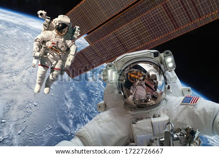 International Space Station and astronaut in outer space over the planet Earth. Elements of this image furnished by NASA. Royalty-Free Stock Photo #1722726667