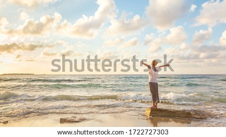 Relaxed woman enjoying sun, freedom and life an beautiful beach in sunset. Young lady feeling free, relaxed and happy. Concept of vacations, freedom, happiness, enjoyment and well being. Royalty-Free Stock Photo #1722727303