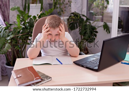 A boy with blond hair in a white T-shirt at the table and does homework on a laptop. Distance learning at home, homework during the epidemic. #1722732994