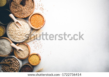 Organic products. Bowls with different gluten free grains on white background, top view Royalty-Free Stock Photo #1722736414