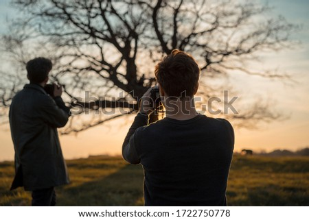 Two photographers take pictures of nature at sunset. #1722750778