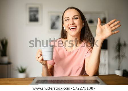 Webcam shot of young positive woman communicates via video communication using a phone, she waving hello at the screen. Self-isolation during quarantine. Video communication, video call Royalty-Free Stock Photo #1722751387