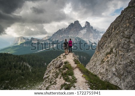Couple of travelers standing on steep ridge, when dark clouds are passing by the slopes of the mountains #1722755941