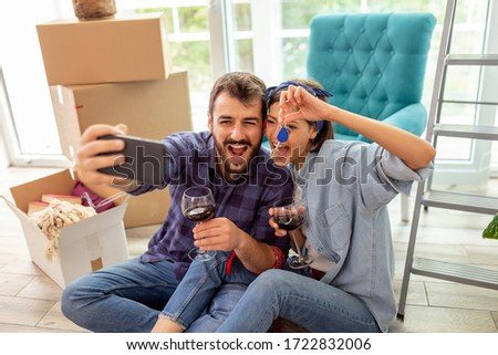 Young couple in love moving in new apartment, drinking wine and having fun taking selfies with apartment keys