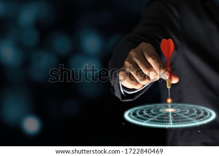Businessman throwing red arrow dart to virtual target dart board. Setup objectives and target for business investment concept. #1722840469