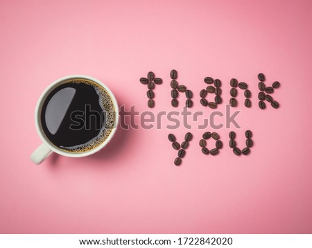 Top view of roasted coffee beans arranged in letters and hot coffee in white coffee cup on pink background for coffee menus or cafe signs  #1722842020