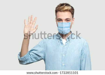 Portrait of happy excited handsome young man with surgical medical mask in blue shirt standing, looking at camera and waving his hand to greeting. indoor studio shot on grey background copy space. #1722851101