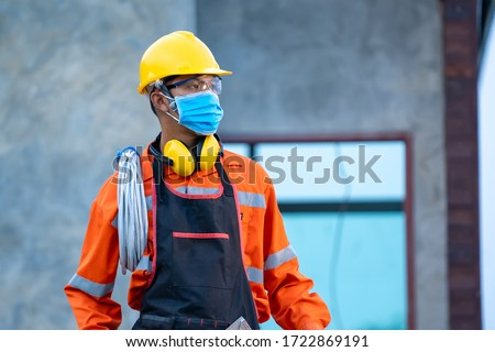 Electrician wearing protective mask to Protect Against Covid-19 and checking production process at the construction site,Engineer,Construction concept,Coronavirus has turned into a global emergency. #1722869191