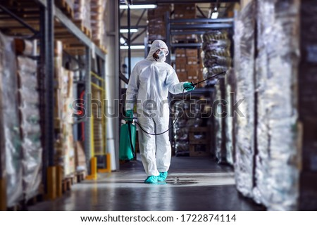 Man in protective suit and mask disinfecting warehouse full of food products from corona virus / covid-19. #1722874114