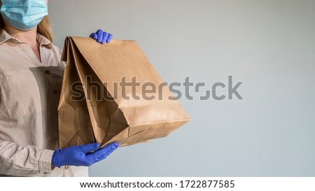 A man in protective gloves and a mask holds packets of food delivered to his home #1722877585