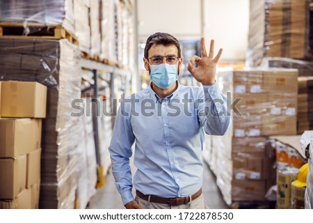 Young businessman with sterile protective mask on standing in warehouse and showing okay sign. Protection from corona virus/ covid-19. #1722878530