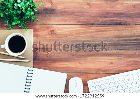 Business background concept. Closeup of coffee cup, notepad, keyboard and mouse on wood table with free space. #1722912559