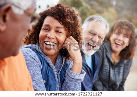 Group Of Senior Friends On Hike In Countryside Talking And Laughing Together #1722921127