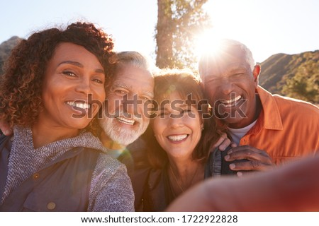 POV Shot Of Senior Friends Posing For Selfie As They Hike Along Trail In Countryside Together #1722922828