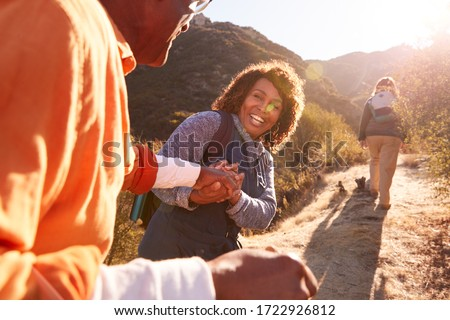 Woman Helping Man On Trail As Group Of Senior Friends Go Hiking In Countryside Together #1722926812