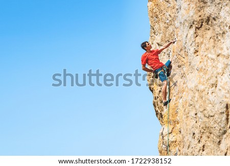 Athletic man climbs an overhanging rock with rope, lead climbing. Sport climbing outdoor. #1722938152