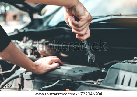 Auto mechanic working in garage Technician Hands of car mechanic working in auto repair Service and Maintenance car check. #1722946204