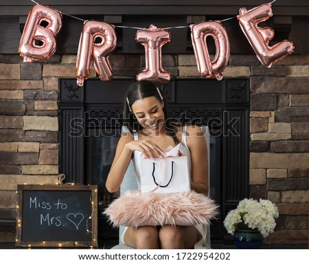 Young smiling African American woman opening a bridal shower present with pink bride balloons and brick fireplace in background Royalty-Free Stock Photo #1722954202