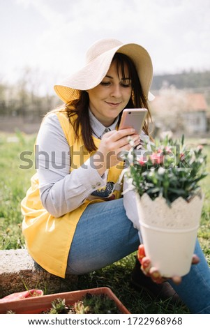 Pretty woman with sun hat taking pictures in garden. Girl holding out of focus pot with plant and taking picture using smartphone during sunny day.