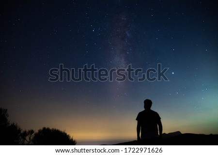 Blurred silhouette of a man observing the starry sky with the milky way Royalty-Free Stock Photo #1722971626