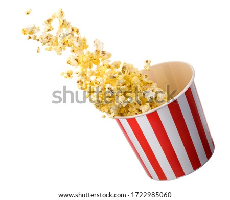 Flying popcorn from paper striped bucket isolated on black background with clipping path. Concept of cinema or watching TV. #1722985060