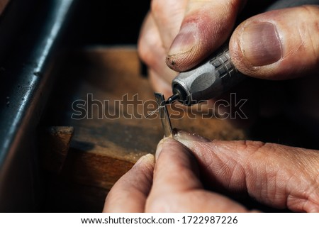 A man's hands work the silver with a drill in a jewelry workshop. The piece of sterling silver is handmade by a goldsmith. #1722987226
